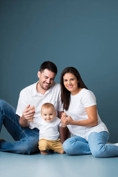 Cute latin young parents sitting and holding baby boy stock photo