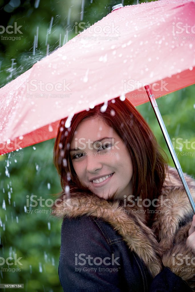 Beautiful Brunette Young Woman Walking in Rain with Umbrella royalty-free stock photo