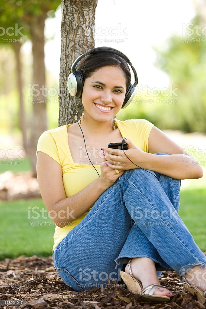 Cute Latino Girl Listening to Portable Music Device royalty-free stock photo