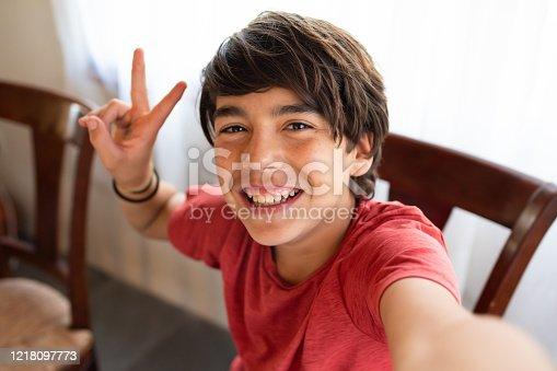 Cute latinx hispanic boy smiling while taking selfie at home