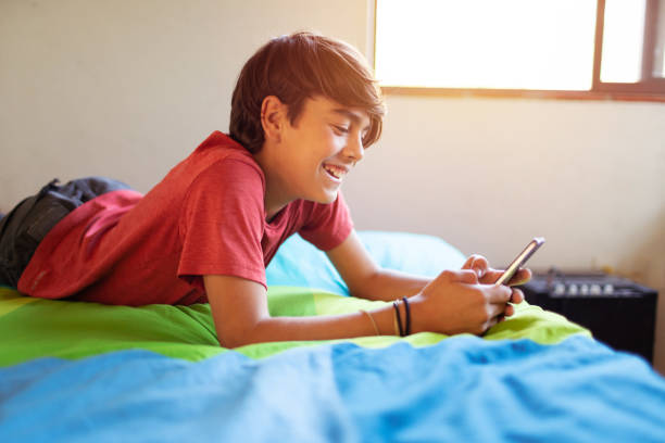 Cute latinx hispanic boy smiling while texting on smartphone in his room stock photo