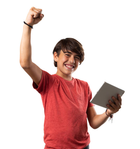 Cute latinx hispanic boy winning with tablet on white background stock photo