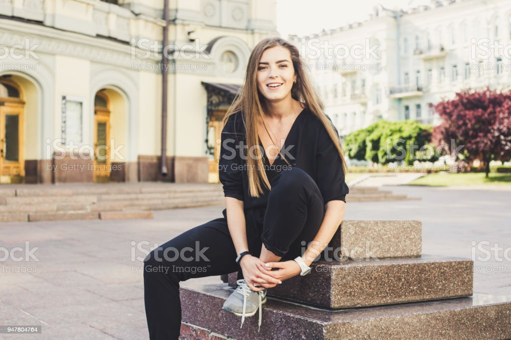 cute laughing model in black jumpsuit sitting at the street and trying to tie shoelaces stock photo