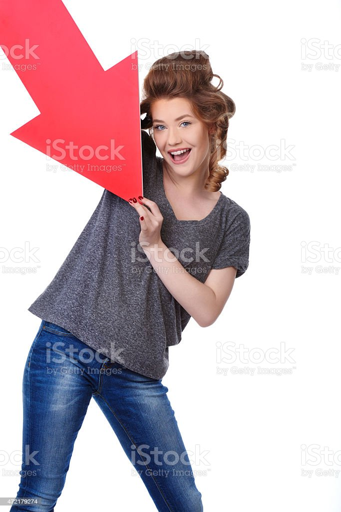cute laughing woman holding arrow sign stock photo