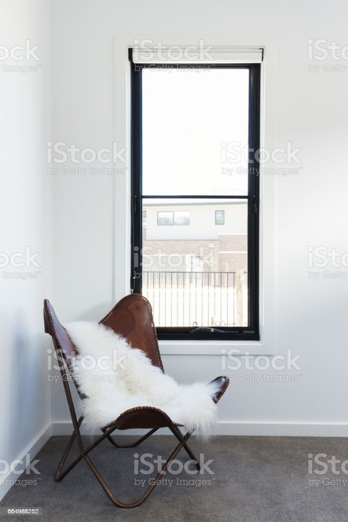 Cute leather chair with sheepskin rug throw in a bedroom stock photo