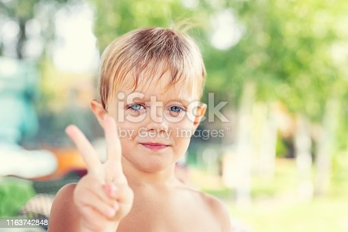 istock Cute liitle caucasian blond boy smiling and showing peace sign with fingers. Child making victory gesture by arm. Happy childhood and summer vacation 1163742848