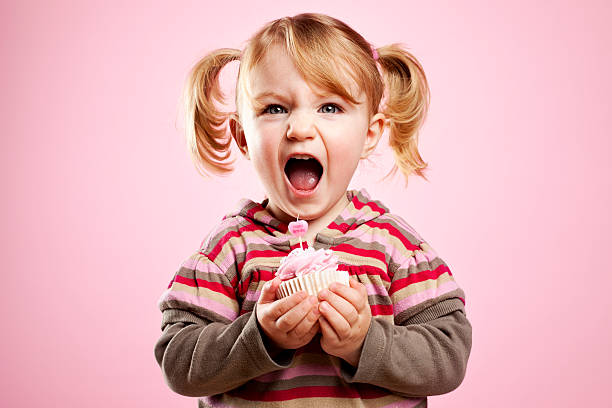 cute litte girl dirty laughing and holding pink birthday cupcake - pigtails stock photos and pictures