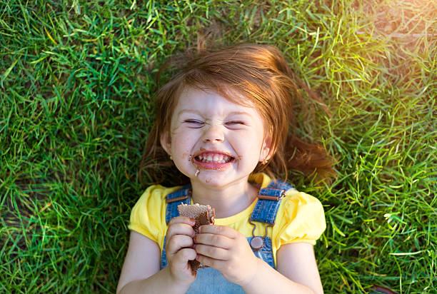 süße litte mädchen - schokoladenplätzchen stock-fotos und bilder