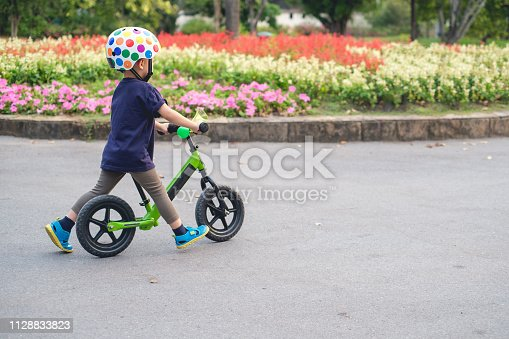 istock Cute little 2 - 3 years old toddler boy child wearing safety helmet learning to ride first balance bike in sunny summer day 1128833823