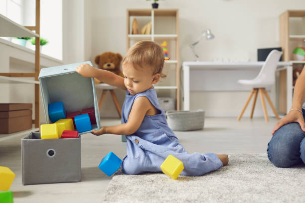 Cute little 2 year old child putting toys back in their place, helping mommy to tidy up stock photo