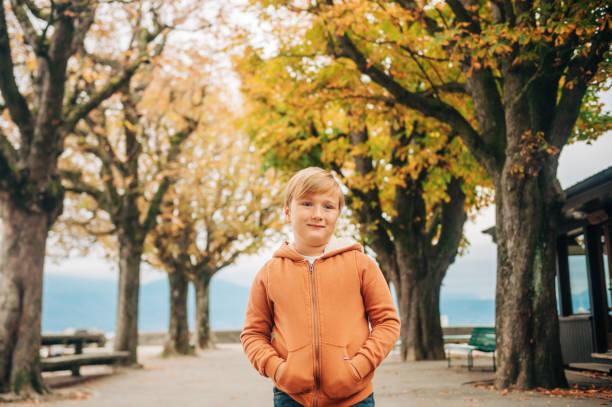 niedliche kleine 7 jahre alten sohn posiert im herbst park tragen orange reißverschluss durch hoody - zip hoodies stock-fotos und bilder