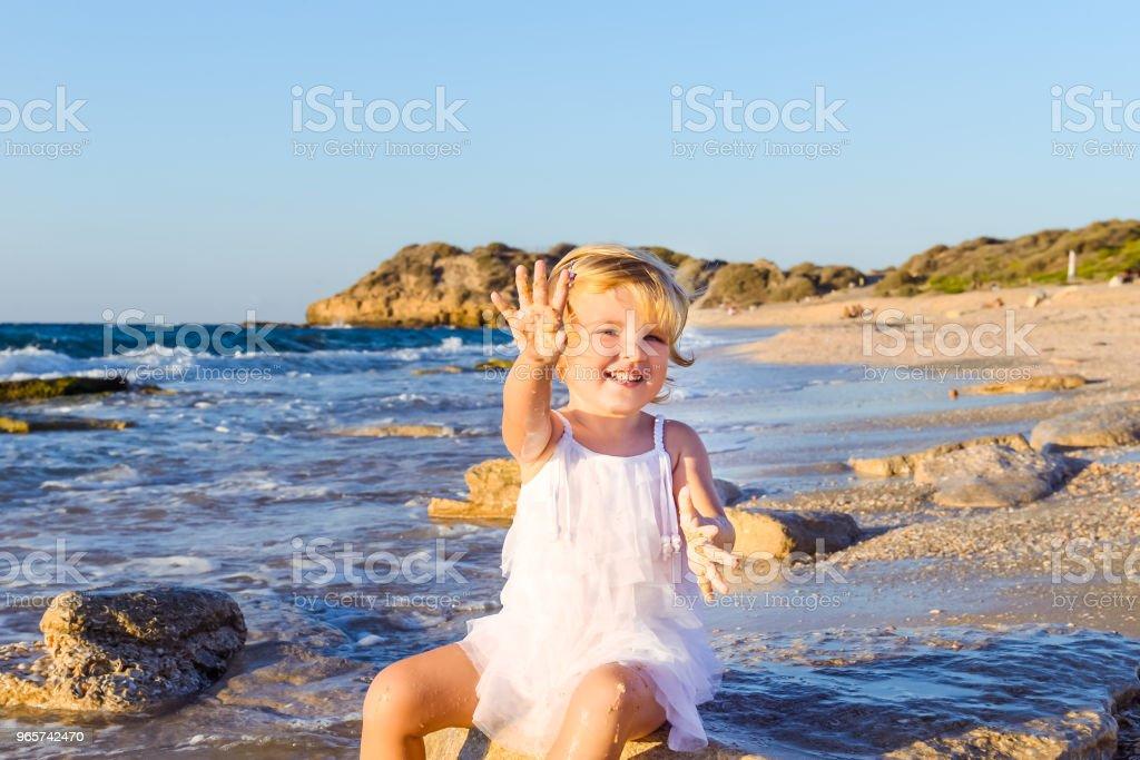 Een schattige kleine schattige kleuter meisje in witte kleren, spelen met zand en schelpen op de lege strand op een warme zonnige zomerdag. Vakantie aan zee. Familie vakantie. Selectieve aandacht, ruimte voor tekst. - Royalty-free Activiteit Stockfoto