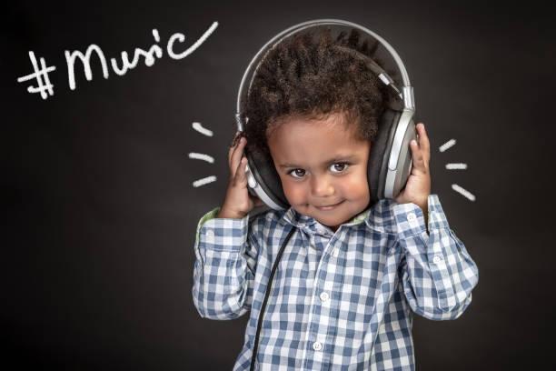 niedlichen kleinen afroamerikanischen jungen tragen kopfhörer - one song training stock-fotos und bilder