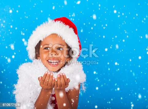 istock Cute little African American girl catching snow flakes 610972178