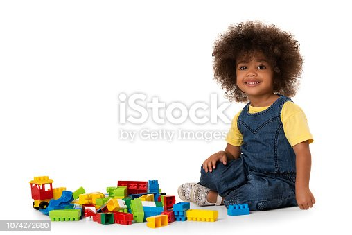 istock Cute little african american girl playing with lots of colorful plastic blocks indoor. Isolated 1074272680