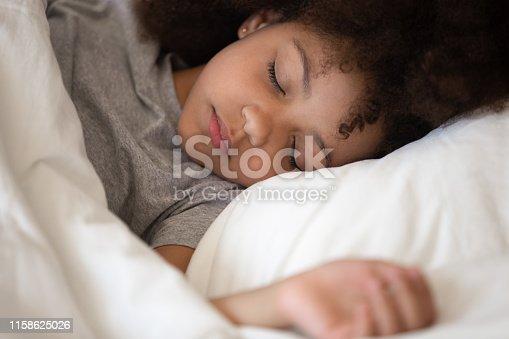 istock Cute little african american kid girl sleeping alone in bed 1158625026