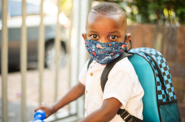 Cute little African boy wearing a face mask riding a toy bike stock photo