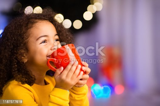 Cute little african girl with cup of hot cocoa sitting near Christmas tree, empty space