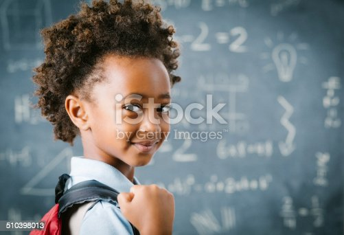 istock Cute little African school girl in classroom 510398013
