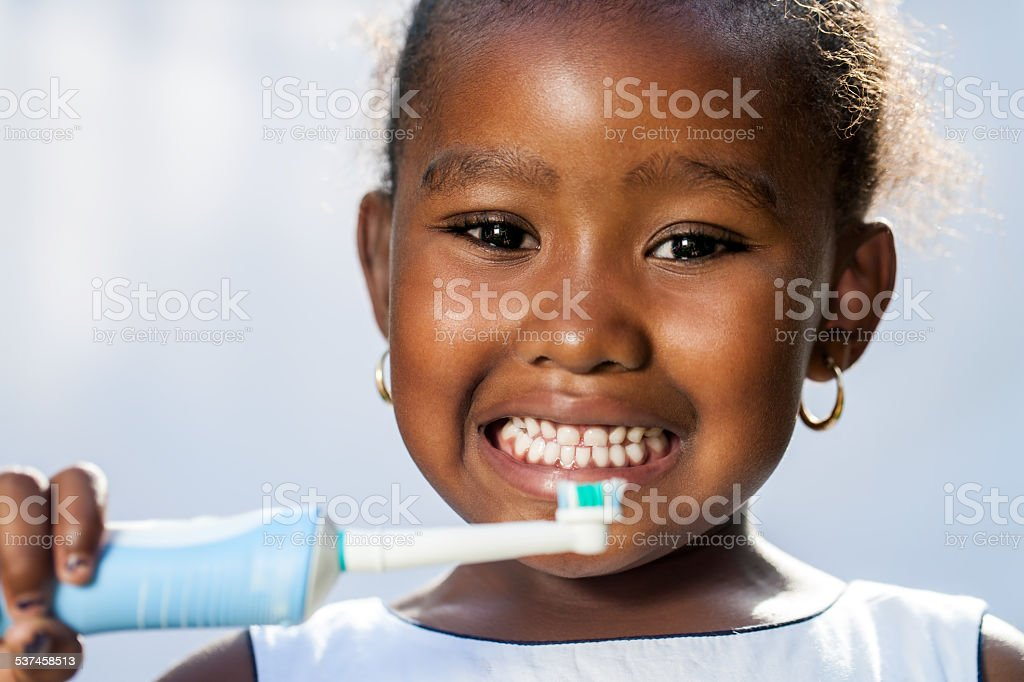 Cute little afro girl holding electric toothbrush. stock photo