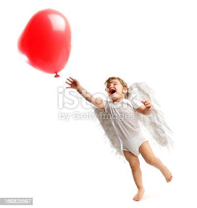 istock Cute little Angel chasing a Heart shaped balloon 186825567