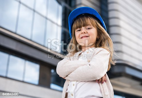 istock Cute little architect with her arms crossed outdoors. 643843490