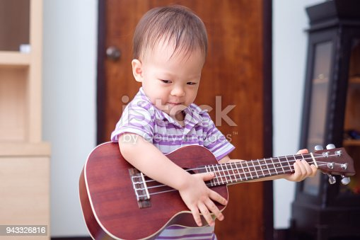 Cute little Asian 18 months / 1 year old baby boy child hold & play Hawaiian guitar or ukulele in living room at home, Music for kids and toddlers concept