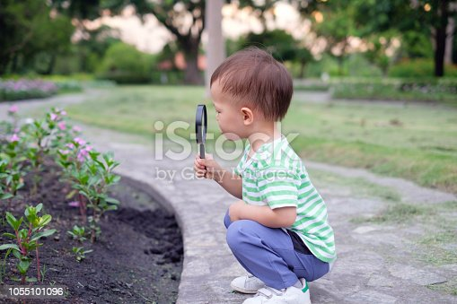 istock Cute little Asian 18 months / 1 year old toddler baby boy child exploring environment by looking through a magnifying glass 1055101096