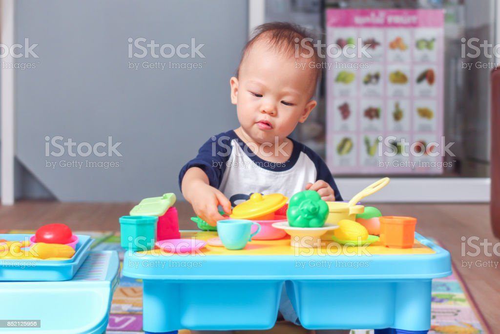 Cute little Asian 18 months / 1 year old toddler baby boy child having fun playing alone with cooking toys in living room at home, stock photo