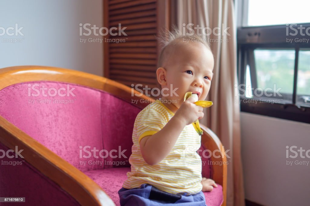 Cute little Asian 18 months / 1 year old toddler baby boy child holding and eating banana in living room at home stock photo
