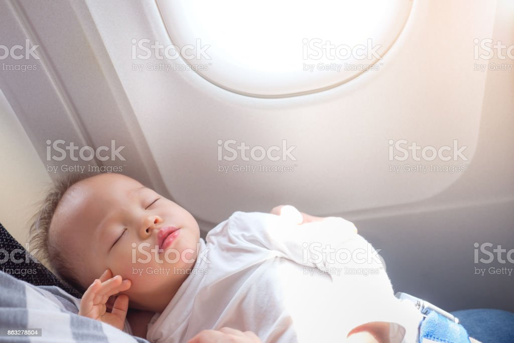 Cute little Asian 18 months / 1 year old toddler baby boy child sleeping on Airplane with copy space stock photo