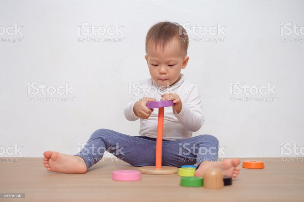 Cute little Asian 18 months / 1 year old toddler baby boy child play with colorful wooden pyramid toy / stacking ring toy stock photo