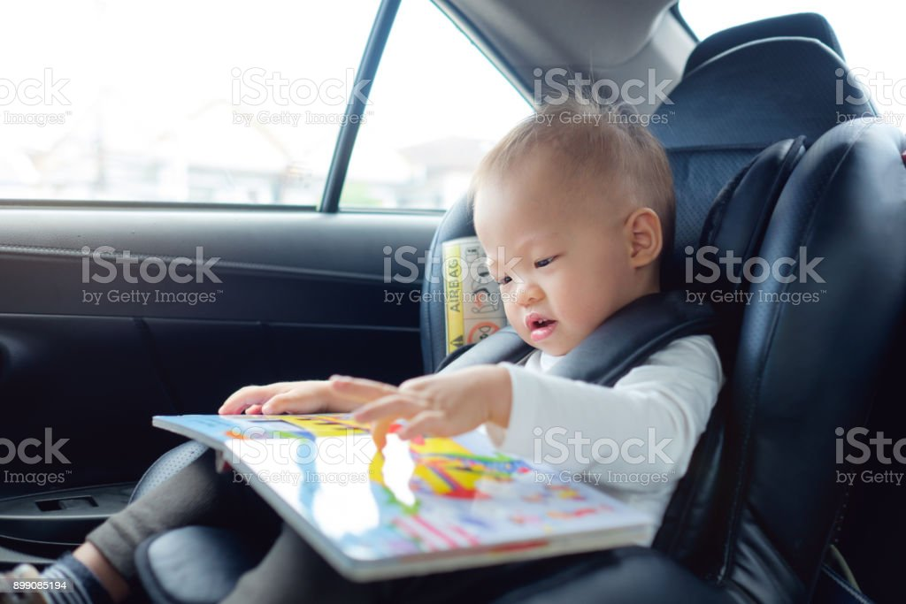 Cute little Asian 18 months / 1 year old toddler baby boy child sitting in car seat holding and enjoy reading book stock photo