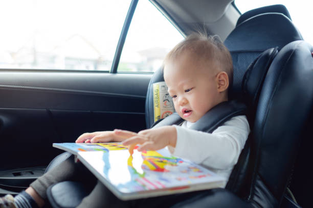 cute little asian 18 months / 1 year old toddler baby boy child sitting in car seat holding and enjoy reading book - asian travel in car stock photos and pictures
