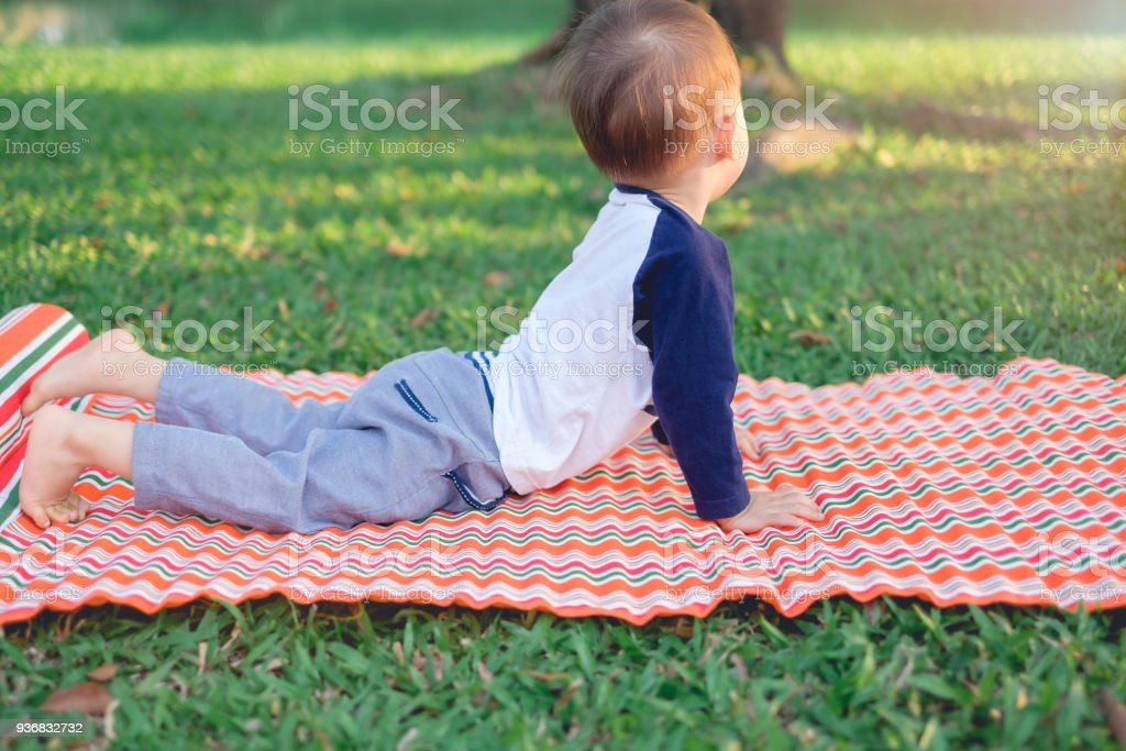 Cute little Asian 18 months / 1 year old toddler baby boy child practices yoga in cobra Pose and meditating outdoors stock photo