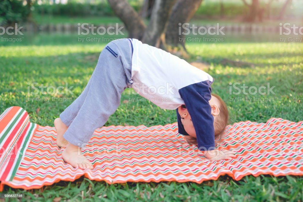 Cute little Asian 18 months / 1 year old toddler baby boy child practices yoga in Downward Facing Dog Pose and meditating outdoors stock photo