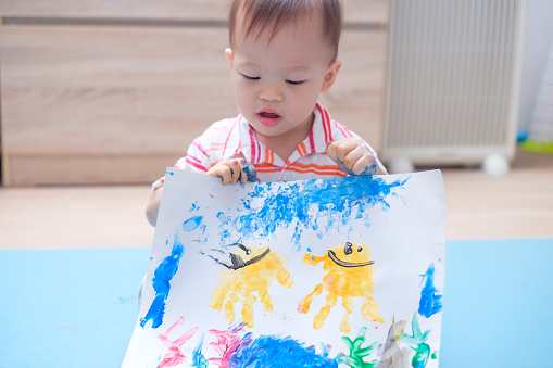1042756824 istock photo Cute little Asian 18 months / 1 year old toddler boy child proudly presenting his finger painting drawing paper 938645194