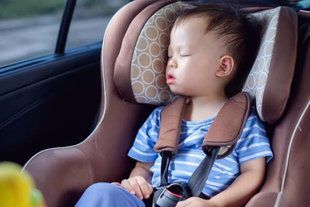 mignon petit asiatique 18 mois/1 an bambin bébé garçon enfant dormant dans le siège-auto moderne. enfant voyageant de sécurité sur la route - child car sleep photos et images de collection