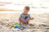 かわいい小さなアジア 18 ヶ月、1 歳の幼児男の子が座って & 遊ぶ子供の姿のビーチの美しい砂浜熱帯サンセットビーチ、家族のおもちゃ旅行、ビーチ休暇の概念に水野外活動