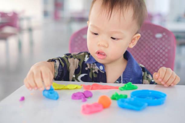 süße asiatische 18 monate alten kleinkind baby junge kindlein spaß spielen bunte modelliermasse / dought in der schule spielen spielen / kinderbetreuung - knete spiele stock-fotos und bilder