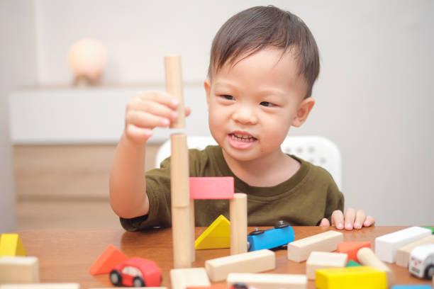 niedliches kleines asiatisches 2-3 jahre altes kleinkind, das spaß am spielen mit holzbauteizeuge im innenbereich hat - 2 3 jahre stock-fotos und bilder