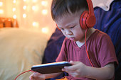 Cute little Asian 2 -3 years old toddler boy child listening to music with headphones from smartphone
