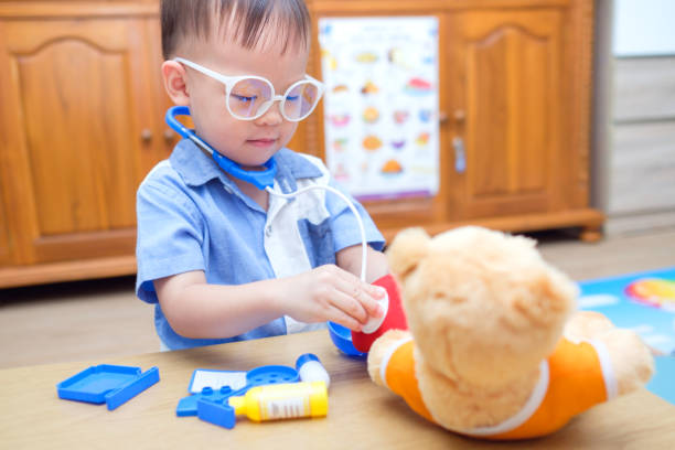 Cute little Asian 2 years old toddler baby boy child concentrate on playing doctor with plush toy at home stock photo
