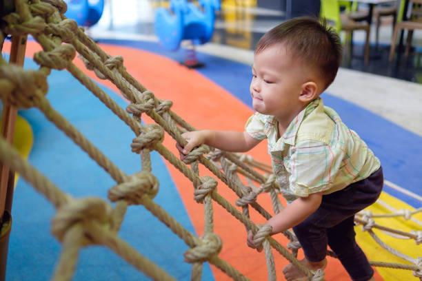 bonito asiáticos 2 anos de idade da criança bebê menino criança divertir tentando subir no trepa-trepa no playground indoor - comodidades para lazer - fotografias e filmes do acervo