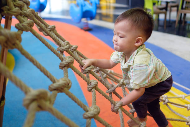 Cute little Asian 2 years old toddler baby boy child having fun trying to climb on jungle gym at indoor playground Cute little Asian 2 years old toddler baby boy child having fun trying to climb on jungle gym at indoor playground, Physical, Hand and Eye Coordination, Sensory, Motor Skills development concept leisure equipment stock pictures, royalty-free photos & images