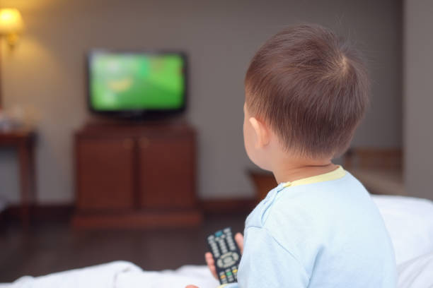 cute little asian 2-3 years old toddler baby boy child sitting in bed holding the tv remote control and watching television - tv e familia e ecrã imagens e fotografias de stock