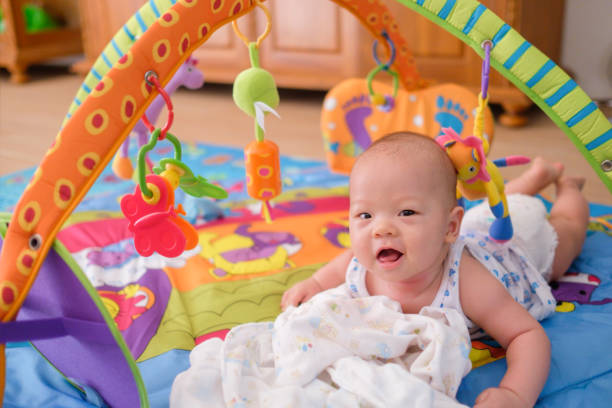 Cute little Asian 5 - 6 months old baby boy child wearing tank top & diaper at tummy time playing toys on play gym on wooden floor in living room stock photo