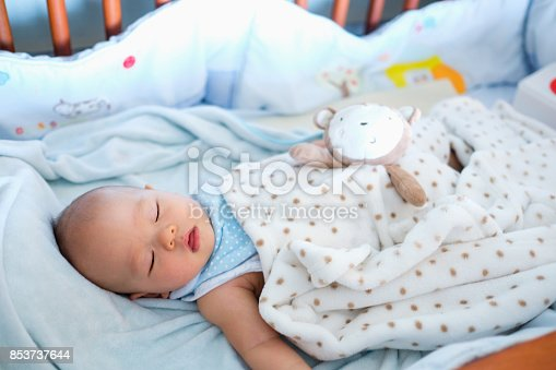 istock Cute little Asian 6 months old  baby boy child sleeping in baby cot / crib in bedroom, Peaceful kid lying on baby bed while sleeping, Daytime sleep concept / Selective focus 853737644