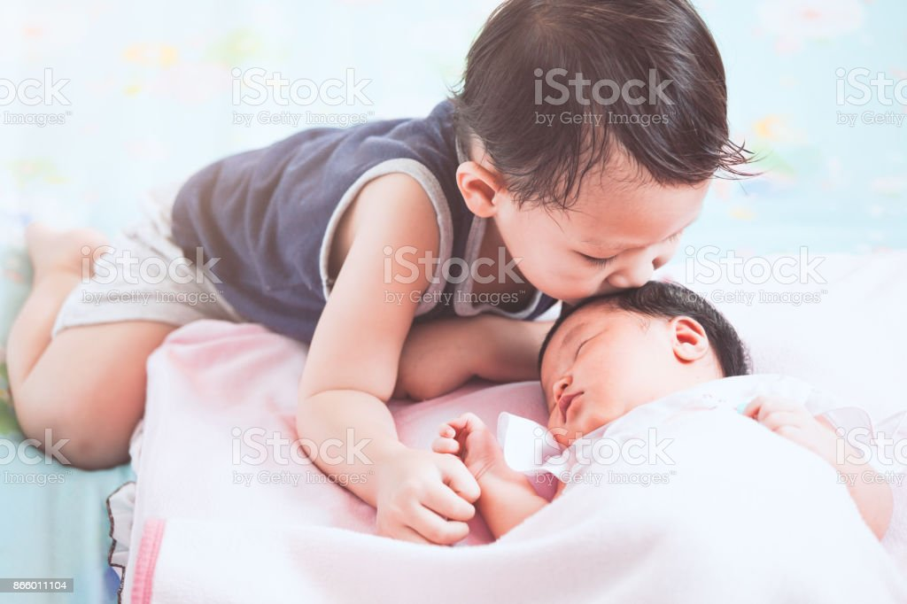 Cute little asian child boy kissing his newborn baby sister with love stock photo