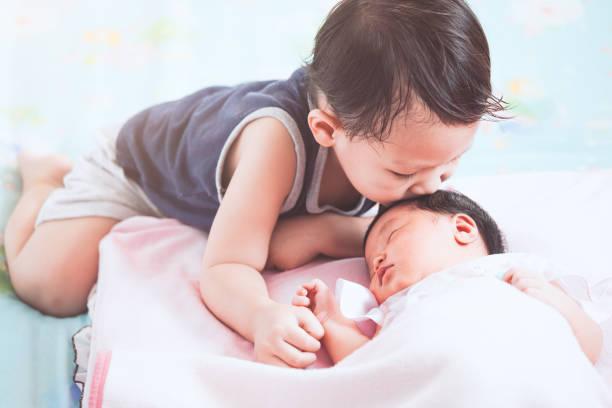 かわいいアジアの子男の子の愛と彼の生まれたばかりの赤ちゃんの妹のキス - 兄弟 ストックフォトと画像